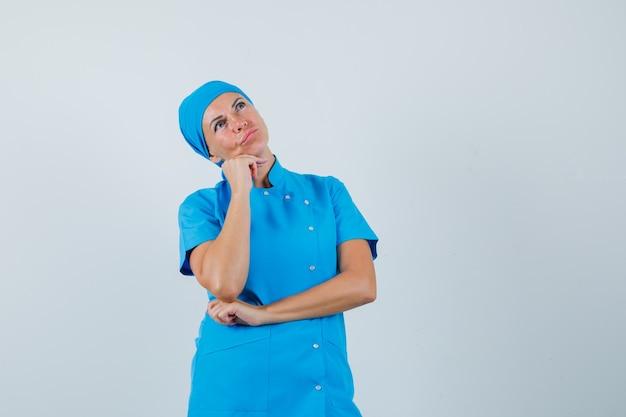 Médica apoiando o queixo na mão em uniforme azul e olhando pensativa, vista frontal.