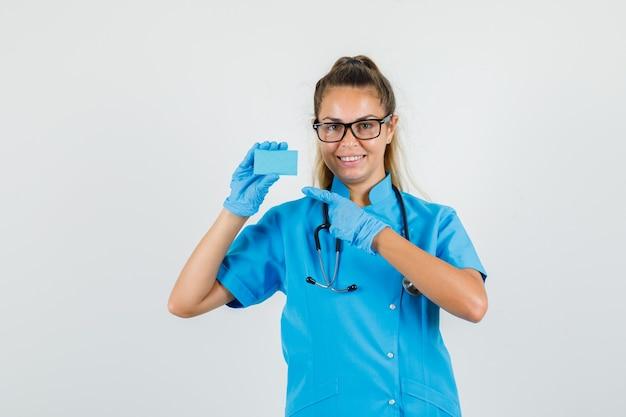 Médica apontando o dedo para o cartão de uniforme azul