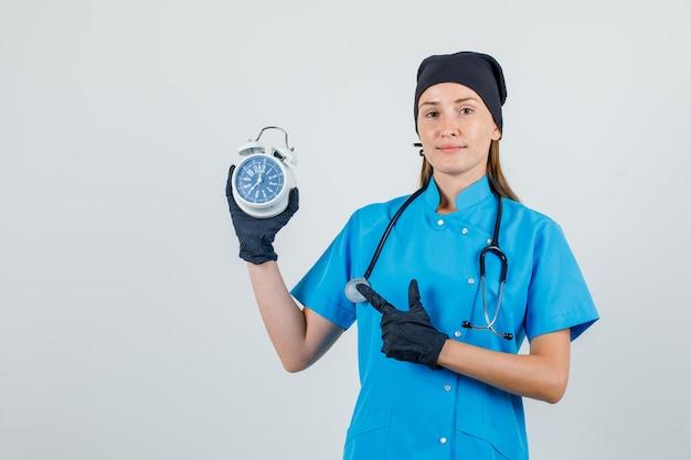 Médica apontando o dedo para o despertador de uniforme, luvas