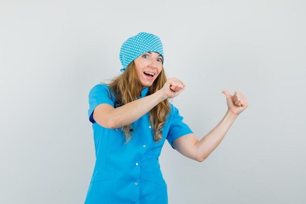 Médica apontando o polegar para cima com uniforme azul e curiosa Foto gratuita