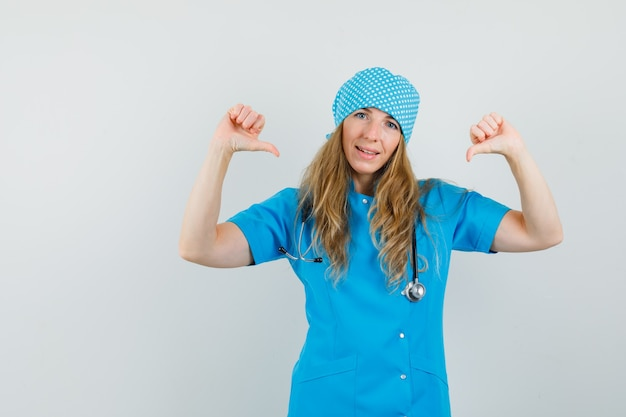 Médica apontando o polegar para si mesma com uniforme azul e parecendo confiante