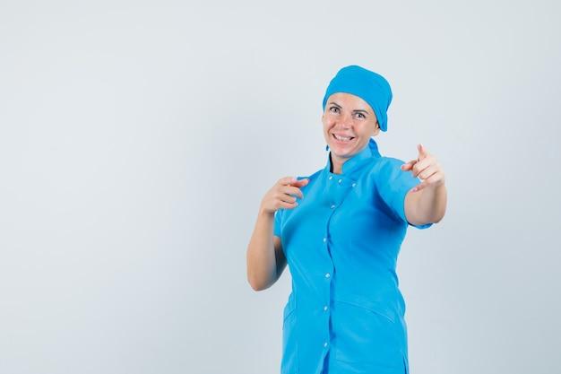 Médica, apontando para a câmera em uniforme azul e parecendo alegre. vista frontal.