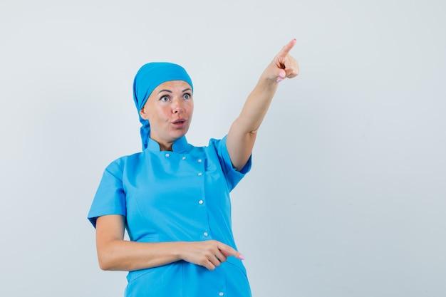 Médica, apontando para algo distante em uniforme azul e olhando espantada, vista frontal.