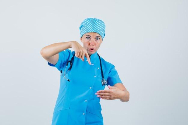 Médica apontando para algo que fingiu estar em uniforme azul e olhando surpresa, vista frontal.