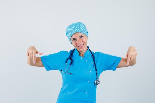 Médica apontando para baixo em uniforme azul e parecendo alegre. vista frontal.