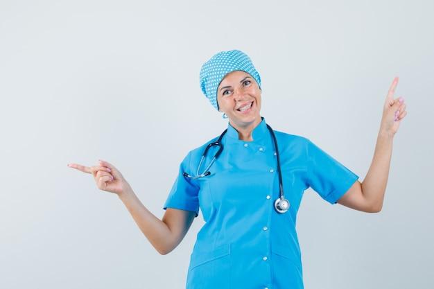 Médica, apontando para longe em uniforme azul e olhando otimista, vista frontal.