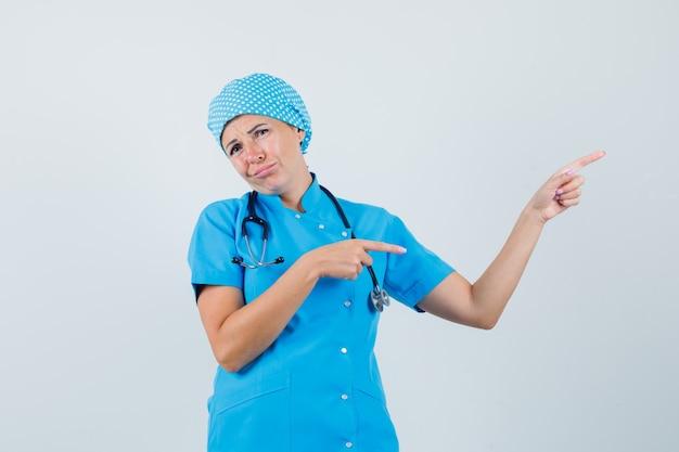 Médica, apontando para o canto superior direito com uniforme azul e parecendo desapontada. vista frontal.