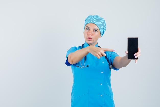 Médica, apontando para o celular em uniforme azul e olhando confiante, vista frontal.