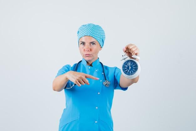 Médica, apontando para o despertador em uniforme azul e olhando séria, vista frontal.