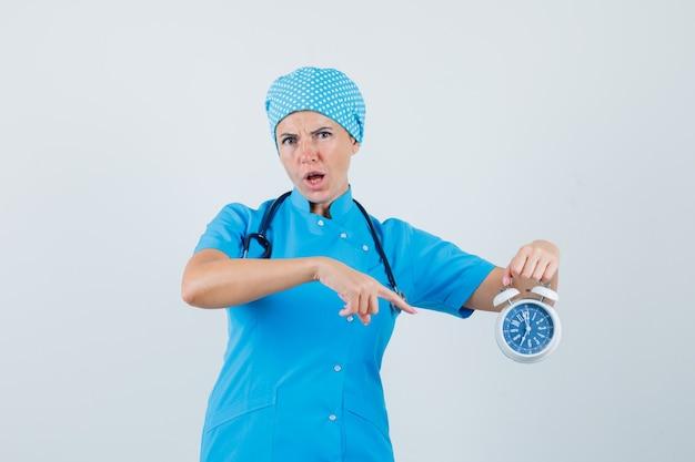 Médica, apontando para o despertador em uniforme azul e parecendo ansiosa. vista frontal.