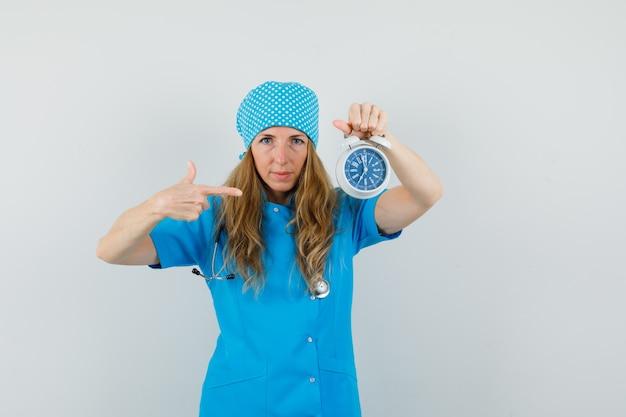 Médica, apontando para o despertador em uniforme azul e parecendo pontual.