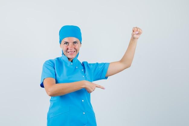 Médica apontando para o lado, fingindo segurar algo na vista frontal uniforme azul.