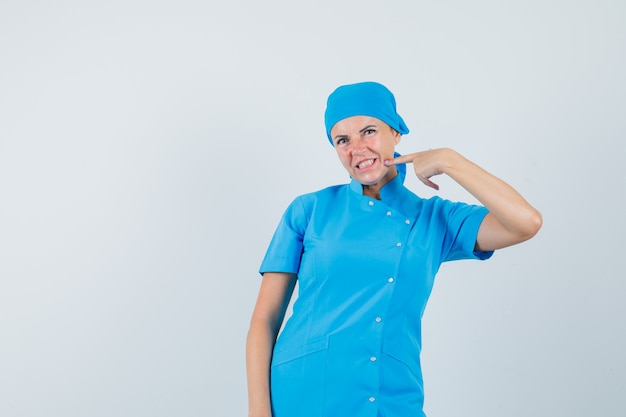 Médica, apontando para o queixo em vista frontal uniforme azul.
