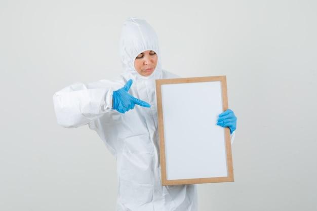 Médica apontando para um quadro em branco em traje de proteção