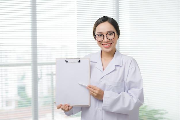 Médica asiática em pé com a pasta no hospital