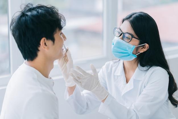 Médica asiática examinando os dentes de um paciente