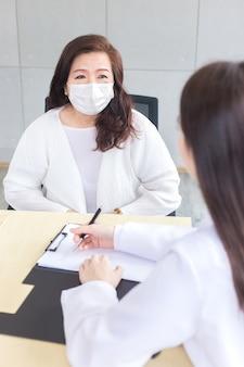 Médica asiática registra o sintoma do paciente no documento enquanto o diagnóstico ambos usam máscara facial