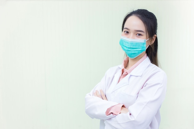Médica asiática usando jaleco branco e estetoscópio no consultório do hospital
