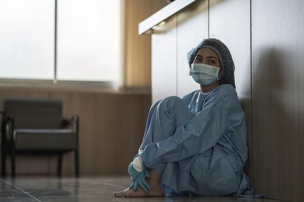 Médica asiática usando máscara cirúrgica sentada no chão, cansada do trabalho devido ao impacto do surto de pandemia covid-19, mulher trabalhadora de saúde de tristeza, conceito médico e de saúde