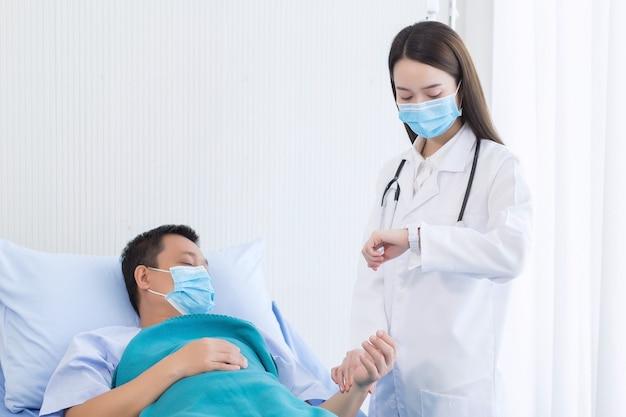Médica asiática verifica o pulso de um paciente do sexo masculino tocando em seu pulso no hospital