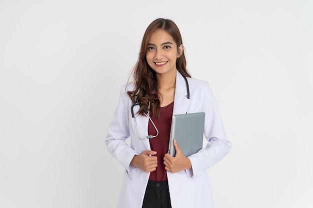 Médica bonita e atraente com cabelo comprido e bom humor, sorrindo, dentes segurando uma almofada