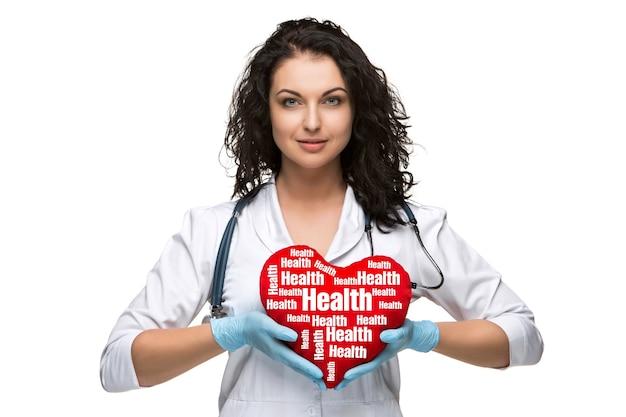 Médica bonita segurando um coração vermelho, isolado no fundo branco