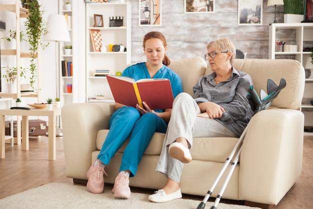 Médica caucasiana, lendo um livro para uma mulher idosa em uma casa de repouso.