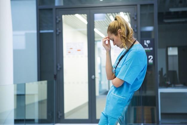 Médica chateada em pé no corredor