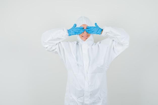 Médica cobrindo os olhos com as mãos em traje de proteção