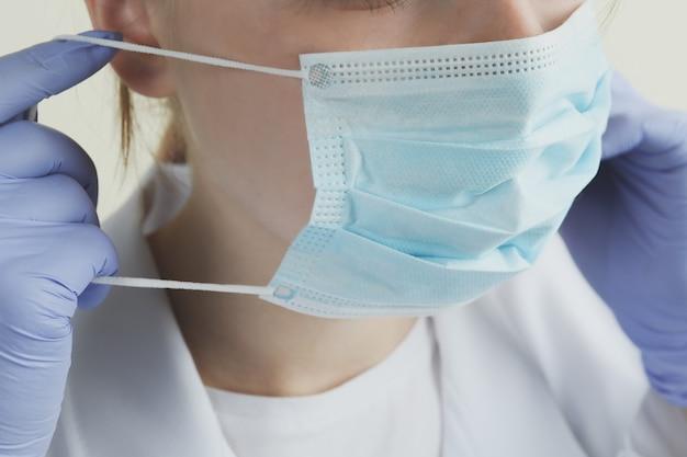 Médica coloca uma máscara, close-up