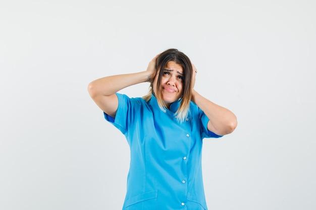 Médica com as mãos nas orelhas com uniforme azul e parecendo irritada
