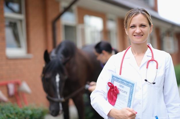 Médica com certificado de exame genético de cavalo de raça pura no estábulo