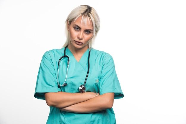 Médica com estetoscópio cruzando os braços em fundo branco. foto de alta qualidade