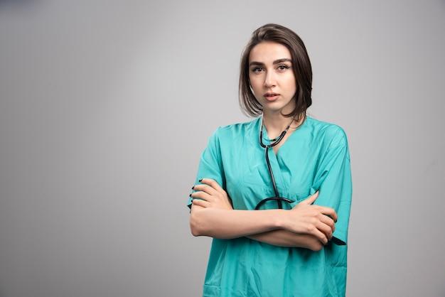 Médica com estetoscópio de pé na parede cinza.