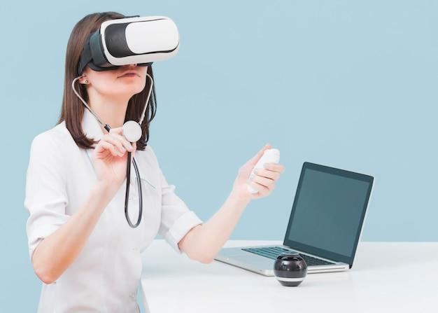 Médica com estetoscópio e fone de ouvido de realidade virtual