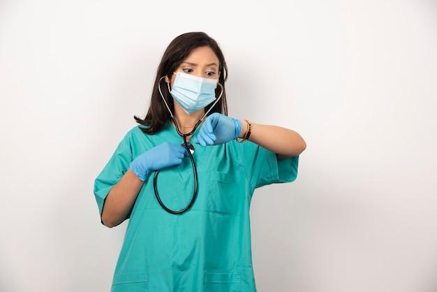 Médica com estetoscópio e máscara, verificando o tempo no fundo branco. foto de alta qualidade