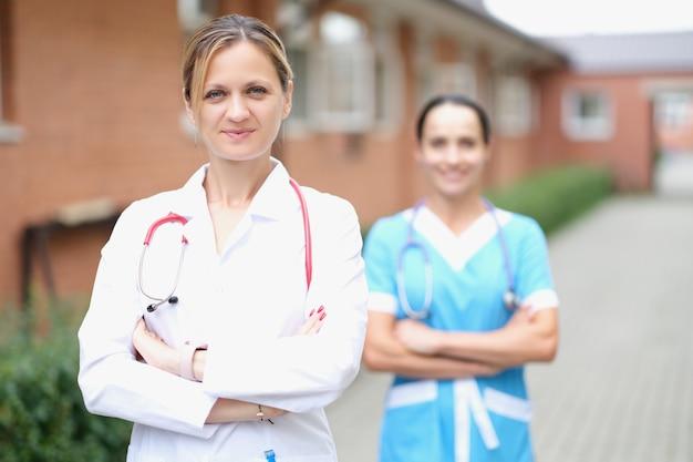 Médica com estetoscópio em pé perto de clínica médica