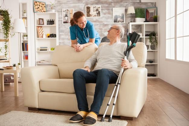 Médica com estetoscópio na casa de repouso, falando com o velho. homem com muletas.