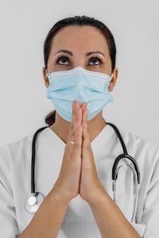 Médica com estetoscópio orando