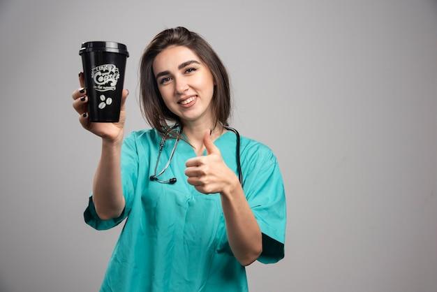 Médica com estetoscópio segurando café e dando polegares para cima.