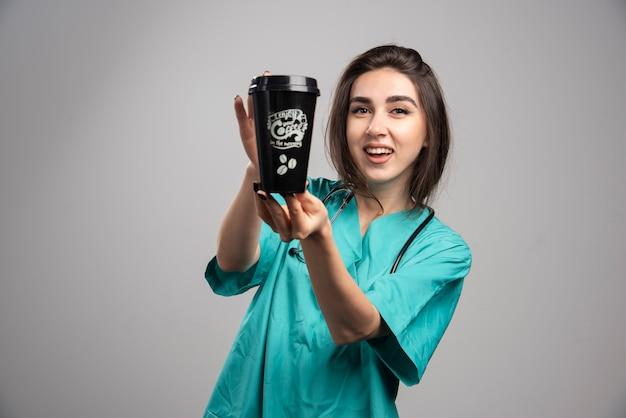 Médica com estetoscópio segurando café.