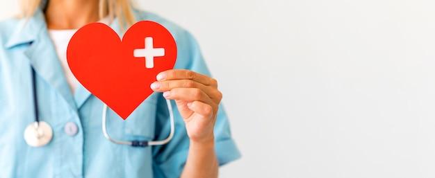 Médica com estetoscópio segurando um coração de papel com espaço de cópia
