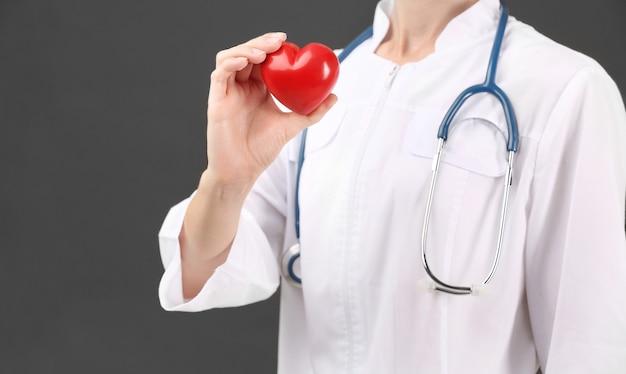 Médica com estetoscópio segurando um coração