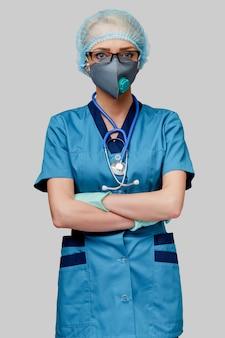 Médica com estetoscópio usando máscara protetora e luvas de látex sobre parede cinza clara
