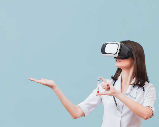 Médica com fone de ouvido de realidade virtual, segurando o tubo de ensaio