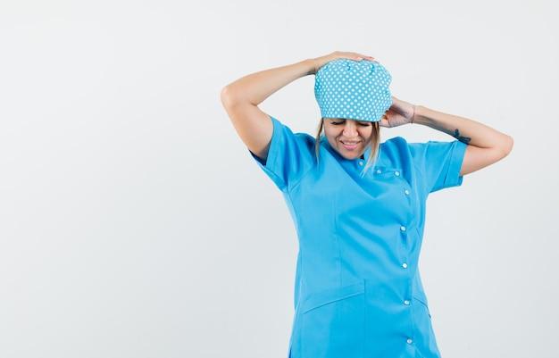 Médica com forte dor de cabeça de uniforme azul e parecendo cansada