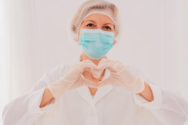 Médica com máscara faz um coração com as mãos