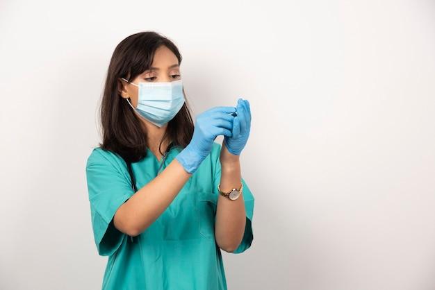 Médica com máscara médica, olhando para um par de luvas em fundo branco. foto de alta qualidade