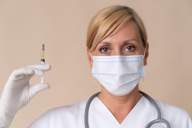 Médica com máscara médica segurando uma seringa de vacina