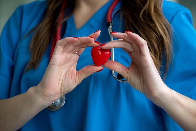 Médica com pequeno coração vermelho, closeup